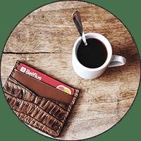 Porte-cartes en cuir pour homme sur table en bois avec café.